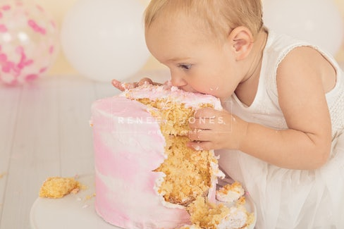 one year old baby girl eating cake during her pink themed cake smash photography session