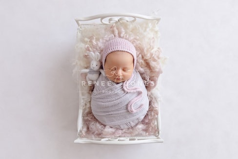 Newborn baby girl wrapped in bed prop