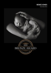 2019 Bronze Award Rise International Photography Award Image Certificate for a black and white portrait of a baby lying on its back curled into her parents arms and hands