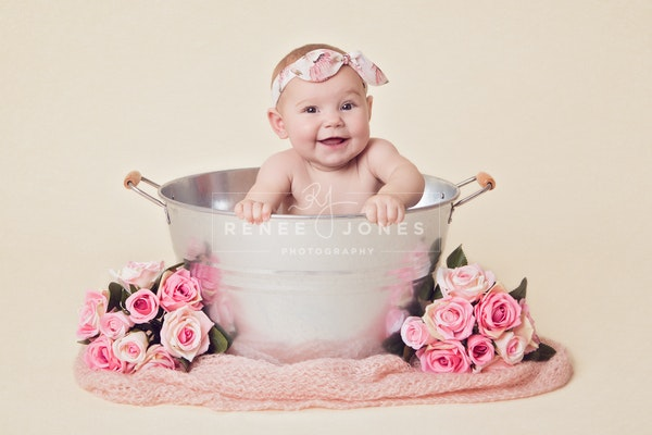 Portrait of a baby girl during her milestone sitter session in a metal tub with pink flowers and fabric