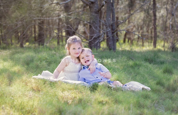 portrait of a boy and girl siblings sitting together in a grassy field