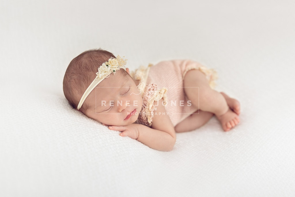 Photograph of a newborn baby girl posed on a white background in a knitted outfit and headband