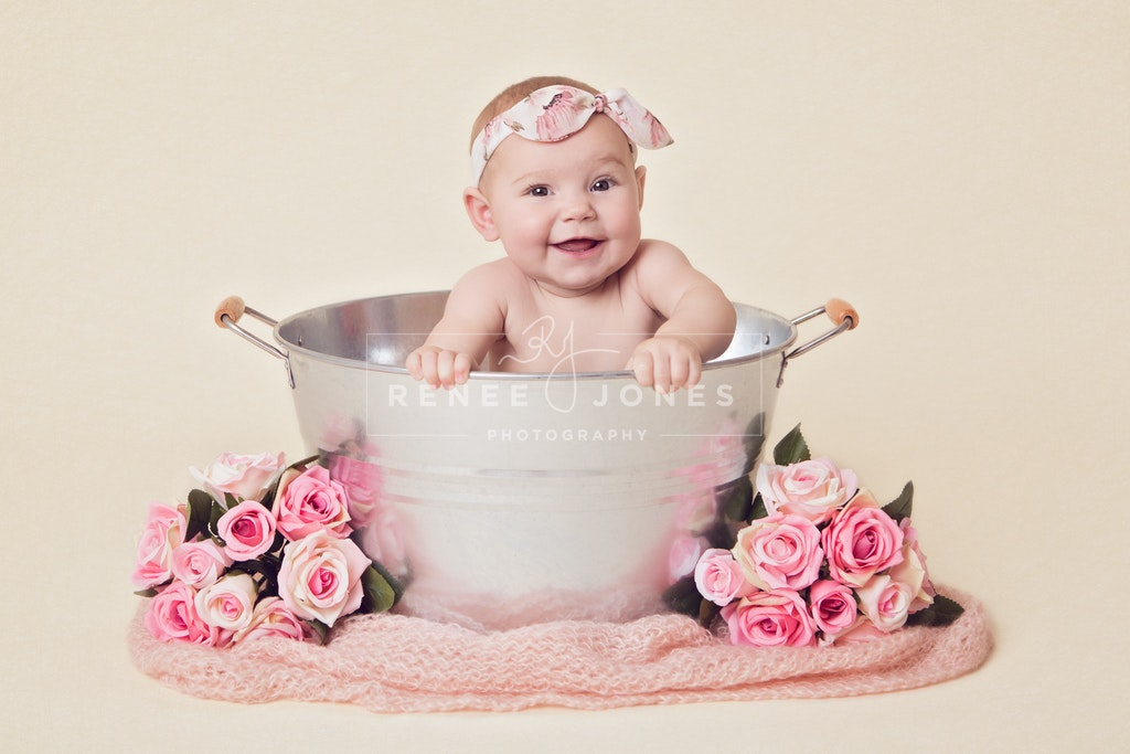 Milestone Sitter session photograph of a smiling baby girl in a metal tub surrounded by pink blanket and flowers