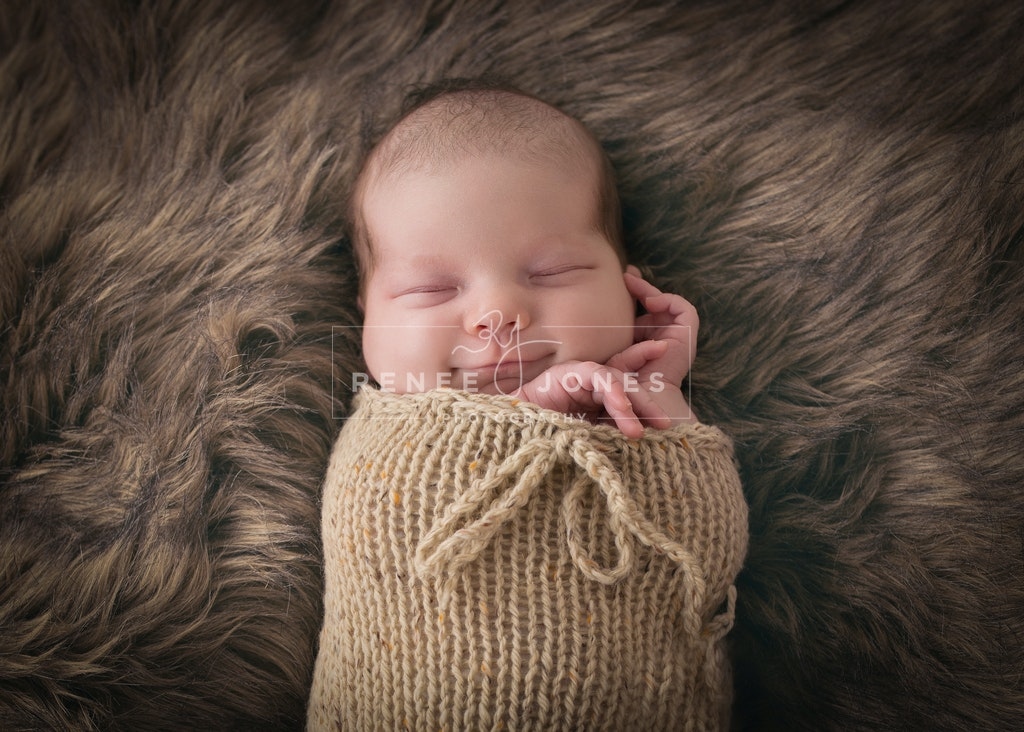 Photograph of a newborn baby in a knitted wrap on a fur rug