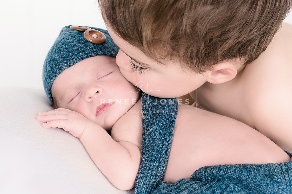 Sibling brother gently kissing his newborn baby brother