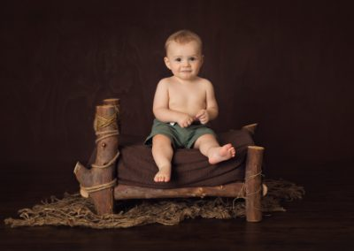 baby boy wearing green shorts on a log bed with brown blanket, rustic jute floor mat on a dark timber brown background
