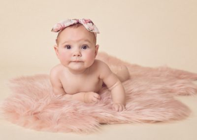 5 month old baby girl portrait, baby girl lying on her tummy on a pink fur rug with a headband