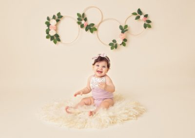 Baby girl dressed in a pink romper smiling and sitting on a cream fur rug with floral wreaths on a cream background