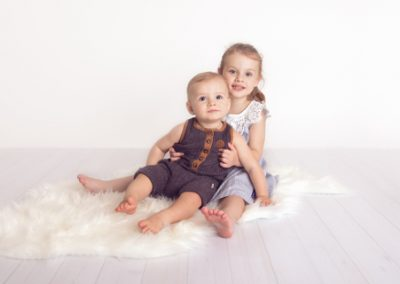 Sibling studio portrait on a white background, white floor boards and white rug. Children are sitting and hugging while looking towards the camera