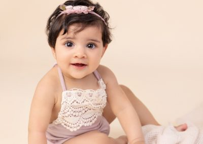 Baby girl dressed in a purple and cream romper sitting on a cream background with cream fabric blanket.