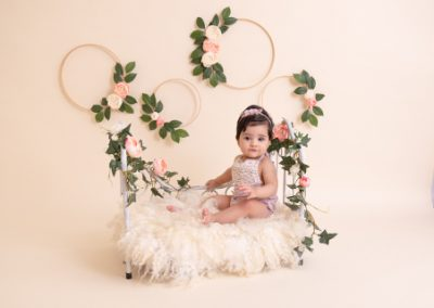 6 month old baby girl sitting on a small metal bed prop on a white curly fur rug with floral wreaths and greenery as a background