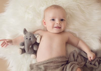 Baby boy headshot portrait, baby lying on his back covered in a brown wrap on a white rug looking up at the camera with a grey elephant teddy.