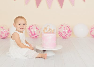 side view of a baby girl dressed in white sitting next to her pink and white first birthday cake, pink and white themed bunting and balloons
