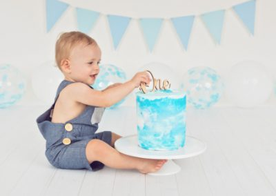side view of a one year old boy in overalls smashing a blue and white cake, blue bunting, blue and white balloons