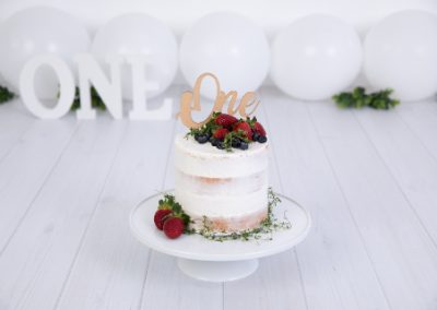 White balloons, white one sign, white naked cake with strawberries, blue berries and greenery set up for a cake smash session