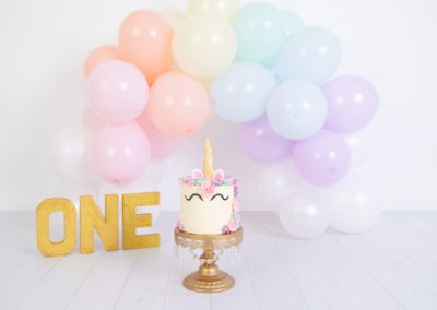 Pastel rainbow balloon garland with a gold 'one' sign and unicorn cake on a gold cake stand