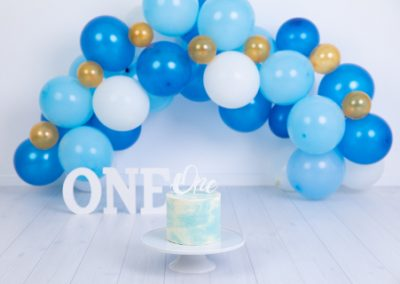 blue white and gold cake smash themed photo with a blue white and gold balloon garland, white one sign and a blue and white cake.