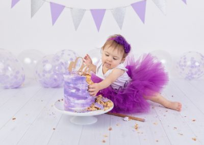 purple themed cake smash with a one year old girl dressed in purple tutu with purple and silver bunting and purple balloons