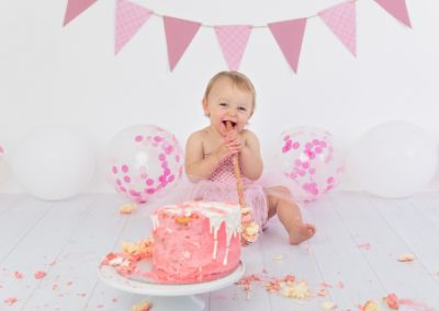 pink and white themed cake smash with a baby girl dressed in a pink tutu, pink bunting, pink and white balloons
