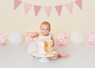 Baby girl eating cake from a wooden spoon during her cake smash session, pink bunting, pink and white balloons