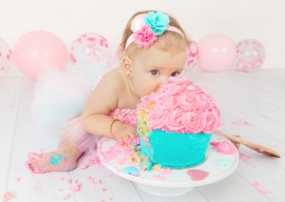 baby girl eating cake with her hands and face, pink and aqua cake smash, pink balloons, pink tutu