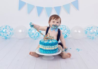 boy with a wooden spoon smashing his first birthday cake during a photography session, blue, white and navy theme, blue bunting, blue balloons