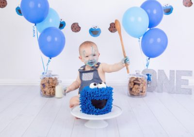 Cookie Monster cake smash with little boy in blue overalls, blue balloons, Cookie Monster cake, cookie jars