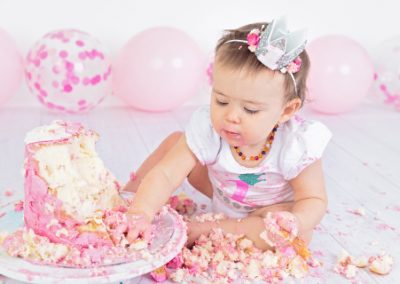 baby girl smashing her cake during first birthday celebration photography session, pink and white theme