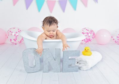 baby in a bath touching the silver letters of the word one, purple, pink and aqua bunting, pink balloons