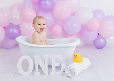 Baby girl in a small clawfoot bath tub, pink and purple balloons, one sign, rubber duck, balloon garland