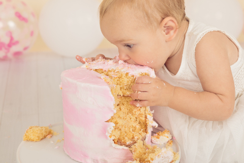 Baby girl holding her birthday cake with her hands and eating it with her mouth against it, pink and white themed cake smash, pink and white cake