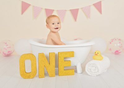 Baby girl sitting and smiling in a small white clawfoot bathtub surrounding by a gold 'ONE' sign, rubber duck, pink bunting and pink and white balloons