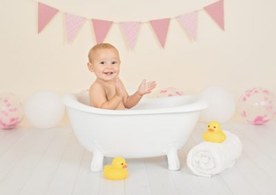 Baby girl clapping her hands while sitting in a small white claw foot bathtub during her photography session, pink bunting and pink balloons, yellow rubber duck