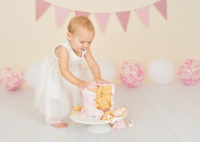 Baby Girl in a white dress standing while she smashes her pink and white cake during her photography session, pink bunting, pink and white balloons