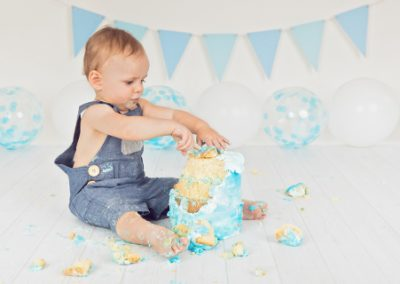 Side view of a baby boy in blue overalls smashing his blue and white cake during his cake smash photography session, blue bunting and blue balloons