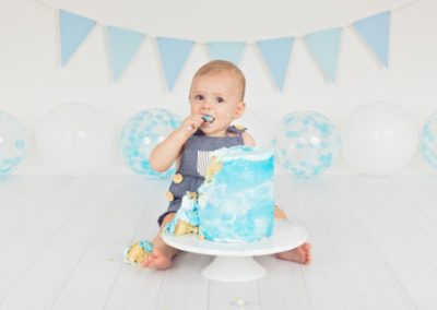 Baby boy about to lick icing from his finger during his blue themed cake smash, blue bunting, blue balloons