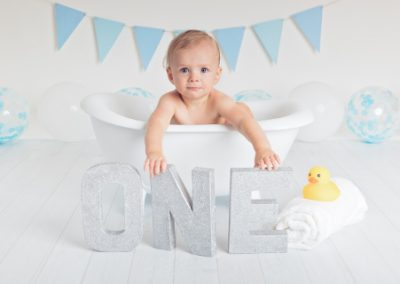 Baby boy in a small white clawfoot bathtub holding a silver 'one' sign with blue bunting, blue and white balloons and rubber duck