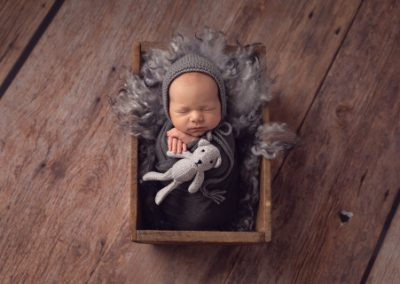 Baby boy dressed in a grey wrap and beanie with a grey teddy bear on a grey fur rug in a rustic timber crate on a wooden backdrop