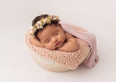 Baby girl wrapped in pink asleep on with her chin on her hands in a white wooden bowl prop on a white background