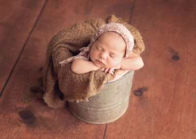 Baby girl wearing a pink bonnet and sleeping upright in a rustic metal bucket