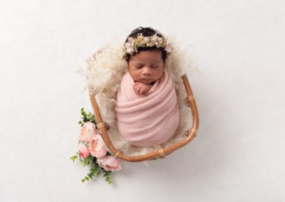 Baby girl wrapped in pink asleep on a cream fur rug in a woven cane basket with pink flowers.