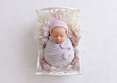 Baby girl wrapped in pale purple fabric with a pink beanie lying in a small metal cream bed with a white fluffy fur rug