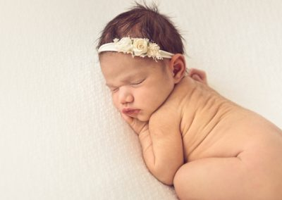 Baby girl asleep on her stomach wearing a cream headband on a cream background, back rolls