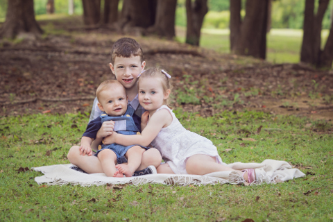 Sibling portrait of a brother, sister and baby brother sitting on a rug on grass with trees cuddling and looking at the camera
