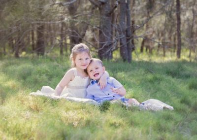 Sibling portrait of a sister and toddler brother sitting on a rug in a grassy field cuddling and looking at the camera