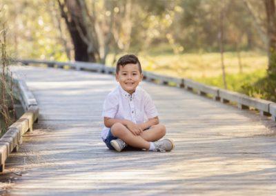 Boy child sitting crossed legs on a boardwalk in a bush background setting.