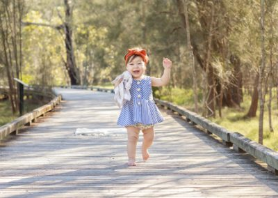 Toddler girl smiling and running toward the camera on a boardwalk in a bushland setting, red headband, blue dress, snuggle toy