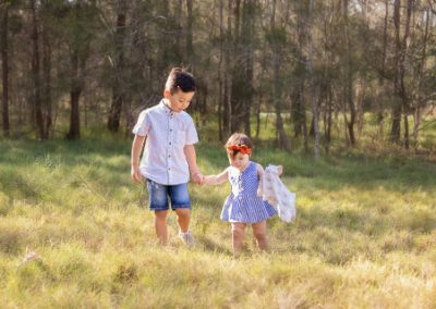 Sibling boy and toddler girl walking through a grassy field holding hands