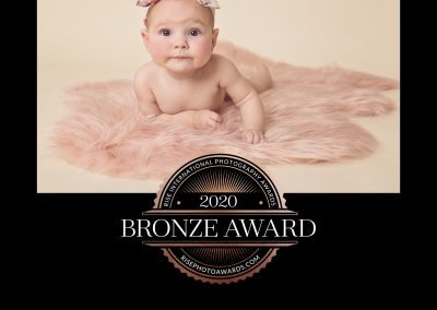 2020 Bronze Award Rise International Photography Award Image Certificate, portrait of a baby girl lying on a pink fur rug while raising her self up on her elbows