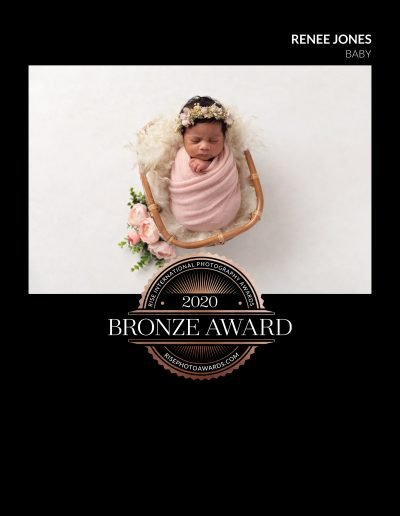 2020 Bronze Award Rise International Photography Award Image Certificate for a baby girl wrapped in pink asleep in an upright position in a woven basket with flowers and cream backdrop